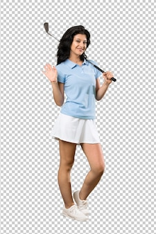 Young golfer woman saluting with hand with happy expression
