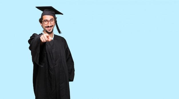 若い卒業した男深刻な遠い外見でアイデアに集中する