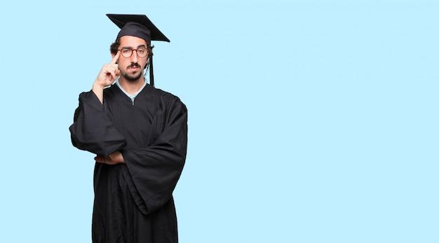 若い卒業した男深刻な表情と下向きのアイデアに集中する