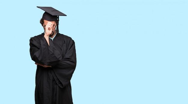 若い卒業した男性深刻な表情でアイデアに集中する