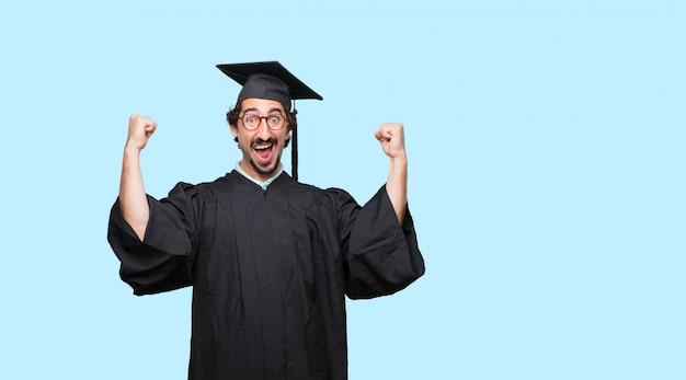 두 검지 손가락으로 얼굴에 미소를 강요하는 젊은 졸업 된 남자