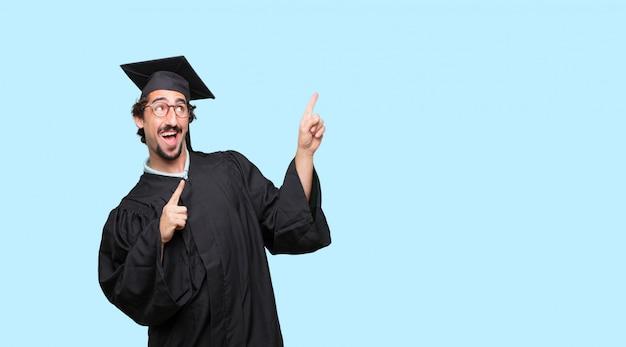 얼굴에 행복하고 자랑스럽고 만족스러운 표정으로 젊은 졸업 된 남자 몸짓 승리