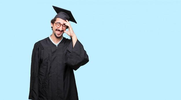 젊은 졸업 남자 머리 뒤로 큰 소리로 웃으면 서 행복하고 쾌활한 표현