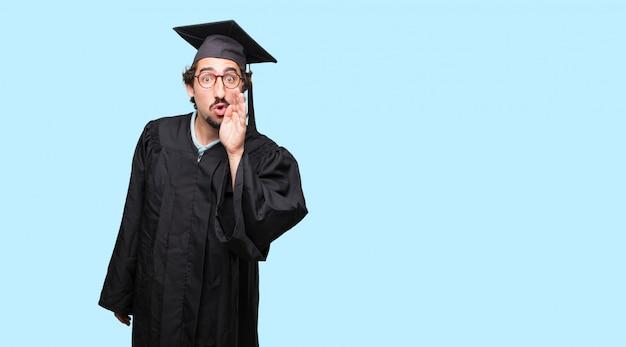 젊은 졸업 남자 앞으로 기울고 얼굴에 심각하고 놀란 표정으로 비밀을 속삭이는