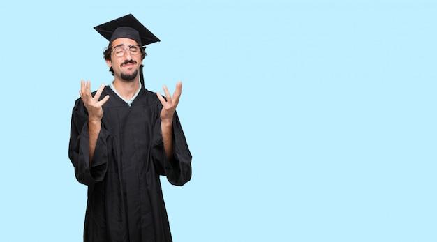 이마에 닫힌 눈과 손으로 스트레스와 좌절을 찾고 젊은 졸업 된 남자