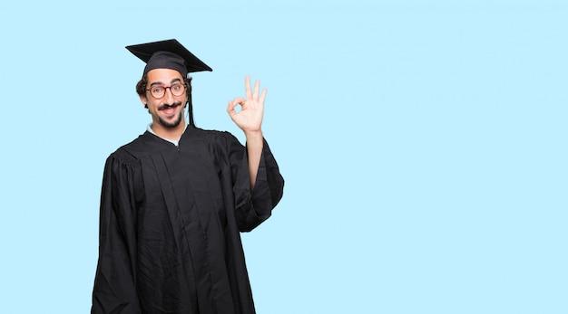 Young graduated man making okay gesture
