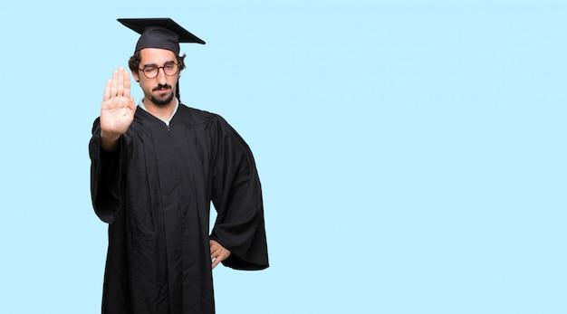 Молодой дипломированный человек сигнализация останавливается ладонью лицом вперед