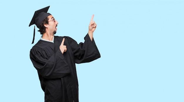 웃 고 양손으로 측면을 가리키는 젊은 졸업 된 남자
