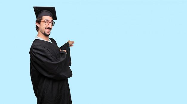 웃 고 양손으로 위쪽을 가리키는 젊은 졸업 된 남자
