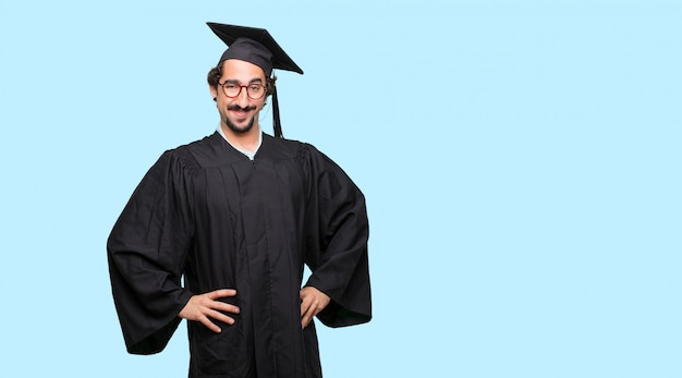 Young graduated man smiling proudly and confidently with arms hands on hips in akimbo pose
