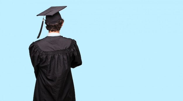 Young graduated man standing sideways, with a proud, satisfied and happy look on face