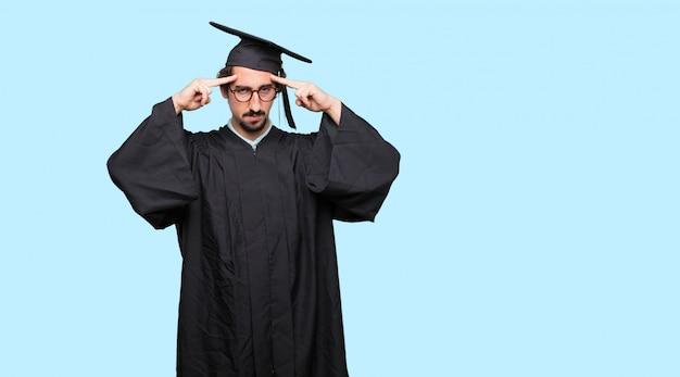 Молодой дипломированный человек с запутанным и вдумчивым взглядом, смотрящим вбок