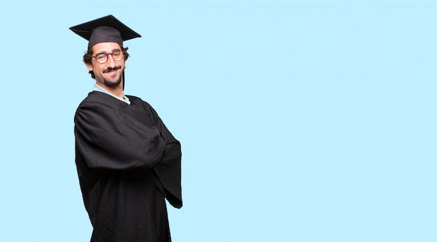 팔을 웃 고 얼굴에 자랑스럽고 만족하고 행복한 표정으로 젊은 졸업 된 남자