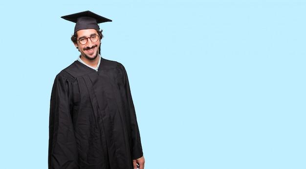엉덩이에 양손으로 자랑스럽고 만족스럽고 행복한 표정으로 젊은 졸업 된 남자
