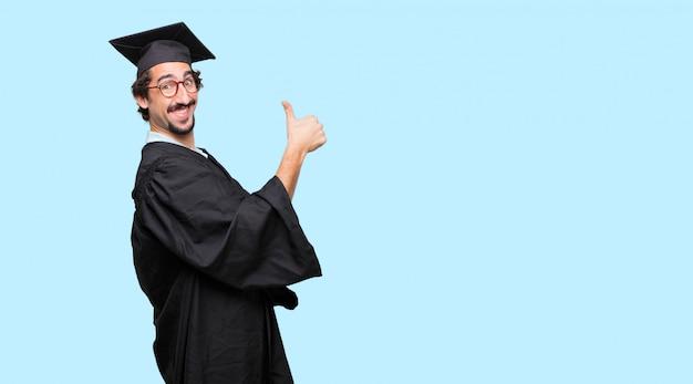 엄지 손가락으로 만족, 자랑스럽고 행복한 표정으로 젊은 졸업 된 남자