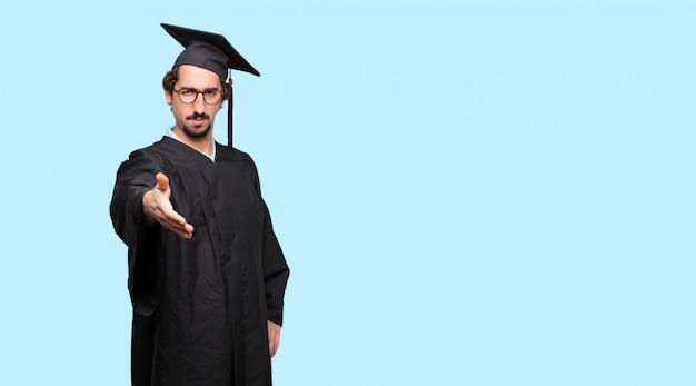 Молодой дипломированный мужчина с серьезным, уверенным, гордым и суровым выражением, предлагающим рукопожатие