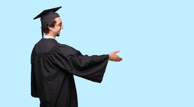 Молодой дипломированный человек с улыбкой, уверенным, гордым, довольным и дружелюбным выражением, предлагающим рукопожатие