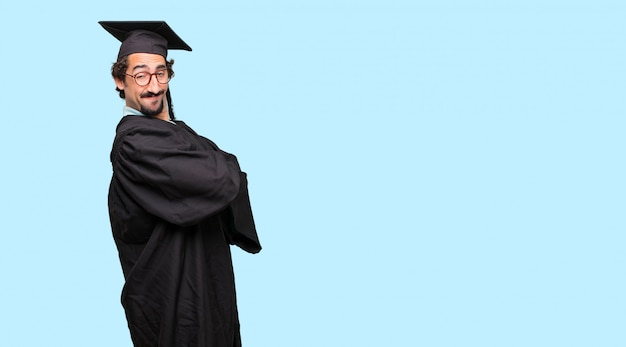 Young graduated man with a proud, happy and confident expression; accepting a challenge