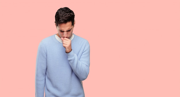Young handsome man coughing, suffering a winter illness such as a cold or the flu