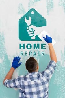Молодой мастер ремонтирует макет стены