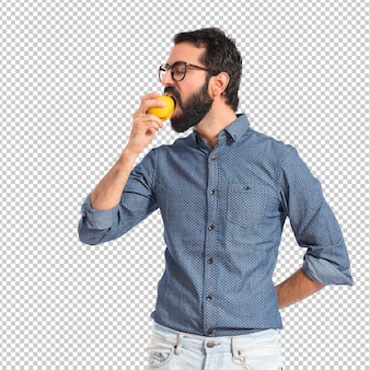 Young hipster man eating apple over white background