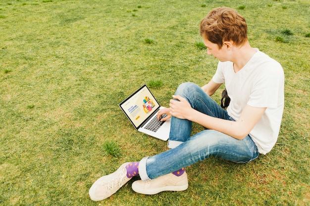 야외에서 노트북에서 일하는 젊은 남성