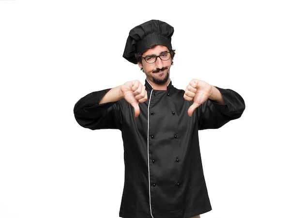 Young man chef with a dissenting, serious, stern expression, with crossed arms in disapproval
