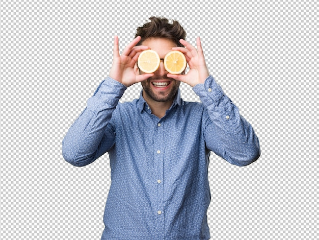 Young man covering his eyes with lemons