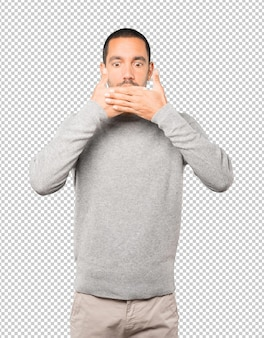 Young man covering his mouth with his hands