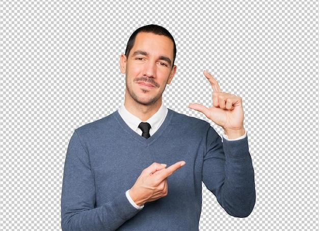 Молодой человек делает жест небольшого размера рукой