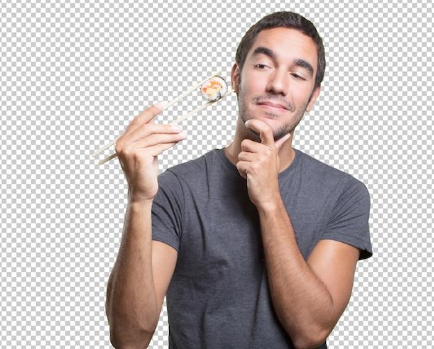 Young man eating sushi