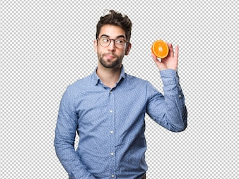 Young man holding an orange