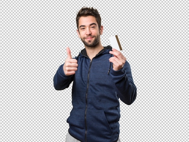 Young man holding a credit card and doing okay gesture