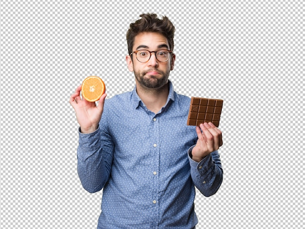 Young man holding an orange and a chocolate bar