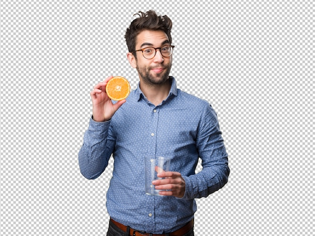 Young man holding an orange and a glass