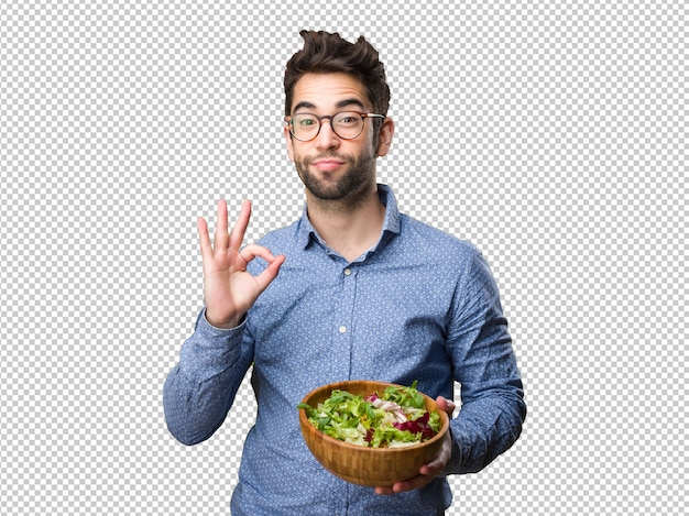 Young man holding a salad doing okay gesture