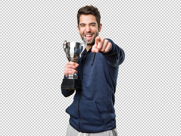 Young man holding a trophy and pointing front