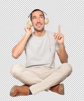 손가락으로 가리키는 제스처와 함께 앉아 위치에 있는 젊은 남자