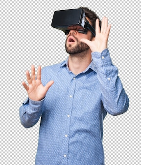 Young man looking through a virtual reality glasses