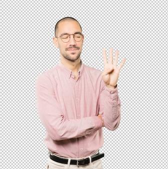 Молодой человек делает жест номер четыре