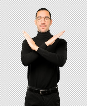 Young man making a gesture of not crossing with the arms