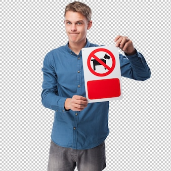 Young man showing a restricted are for dogs sign