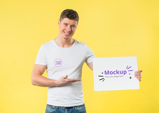 Giovane uomo in piedi e mostrando un mock-up