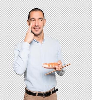 Young man using chopsticks to eat sushi