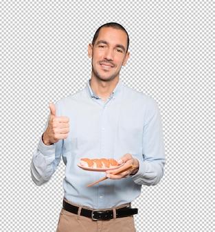 箸を使って寿司を食べる青年