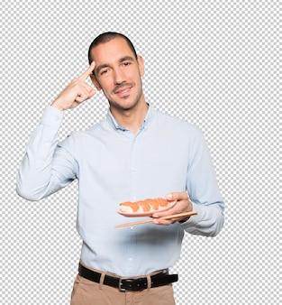 Молодой человек, используя палочки для еды, чтобы съесть суши