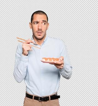 젓가락을 사용하여 초밥을 먹는 젊은 남자