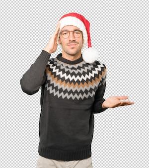 Молодой человек в новогодней шапке, жестикулируя изолированные