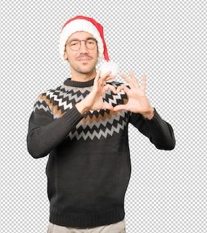 孤立したジェスチャーをしながらクリスマスの帽子をかぶって若い男