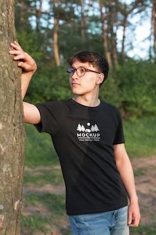 숲에서 모형 티셔츠를 입은 청년